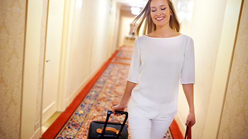 Lady in hotel hallway with luggage