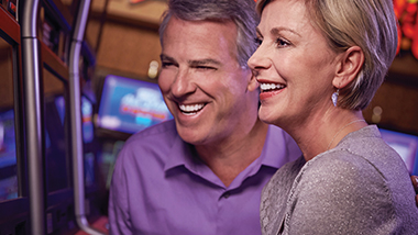 smiling man and woman at slot machine