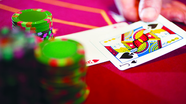 Blackjack cards on red table with gaming chips