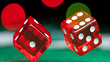 pair of red dice being thrown on green craps table felt