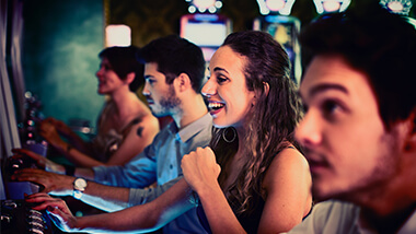 Girl celebrating a win at the slot machines with people surrounding her