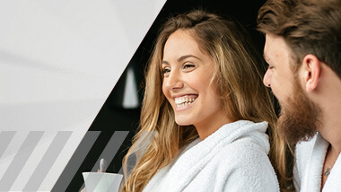 Woman and man in bathrobes laughing.